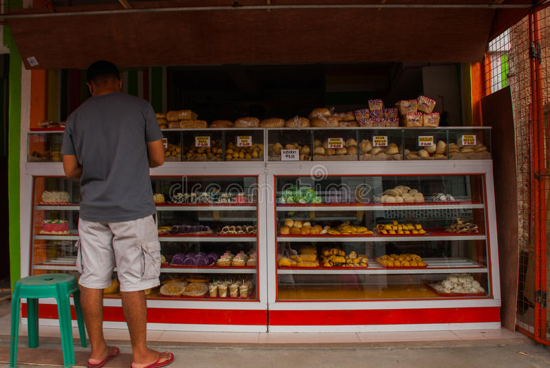 Display window of a bakery and pastry shop of with variety of baked goods, breads, donuts, puff pastry, closeup. Philippines. royalty free stock photo