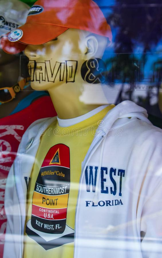 Display in window of shop showing male mannequin wearing Key West teeshirt and jacket and cap with tropical scene reflected Key We stock image