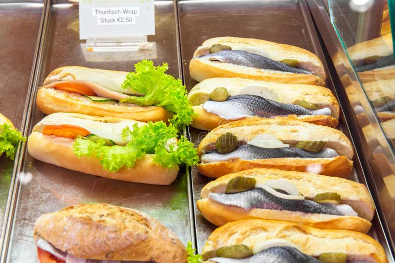 Display window show case of a bakery and pastry shop with assortment of healthy fast food sandwiches with salmon herring stock images