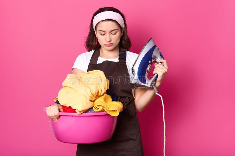 Displeased attractive young female standing isolated over pink background in studio, holding iron and basin with clean clothes in. Both hands, looking at stock image
