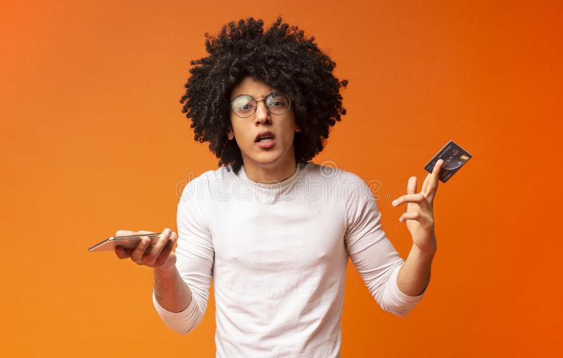 Displeased black guy shrugging with credit card and phone. No money on smartphone. Displeased black guy shrugging and lifting eyebrows in despair, showing credit stock image