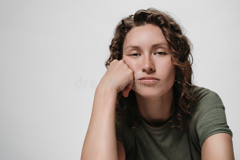 Displeased cansou a mulher encaracolado sonolento, sustentando seu mordente, olhando furado fotos de stock