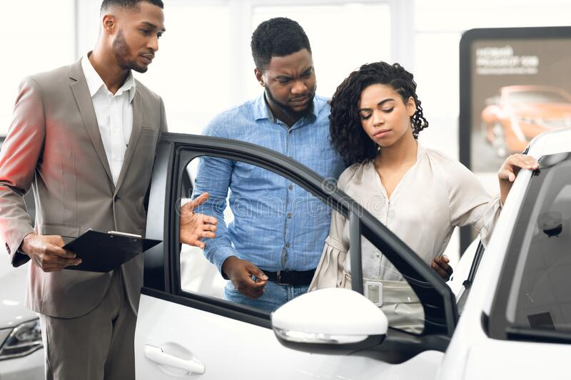 Displeased Car Buyers Choosing Automobile With Seller In Dealership Store. Displeased Car Buyers Looking At Auto Choosing New Automobile With Seller Man In royalty free stock photography