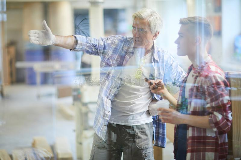 Displeased carpenter foreman scolding young subordinate stock photos