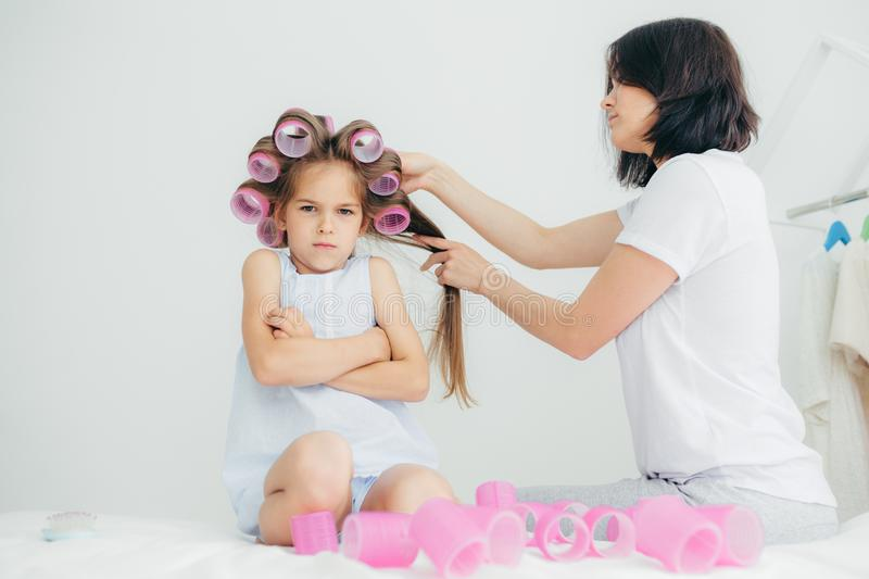 Displeased child keeps hands crossed, looks with sullen expression, being discontent as her mother winds curlers on her hair, does royalty free stock images
