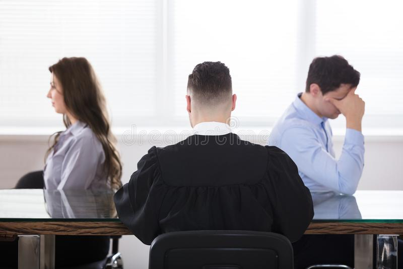 Judge Sitting With Displeased Couple stock photo