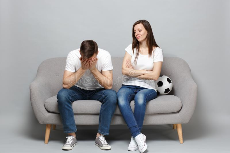 Displeased couple woman man football fans cheer up support favorite team with soccer ball covering face with hands stock photos