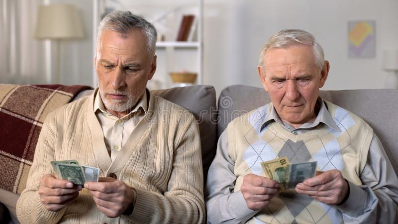Displeased elderly men counting dollars, low social payment, financial crisis. Stock photo royalty free stock images