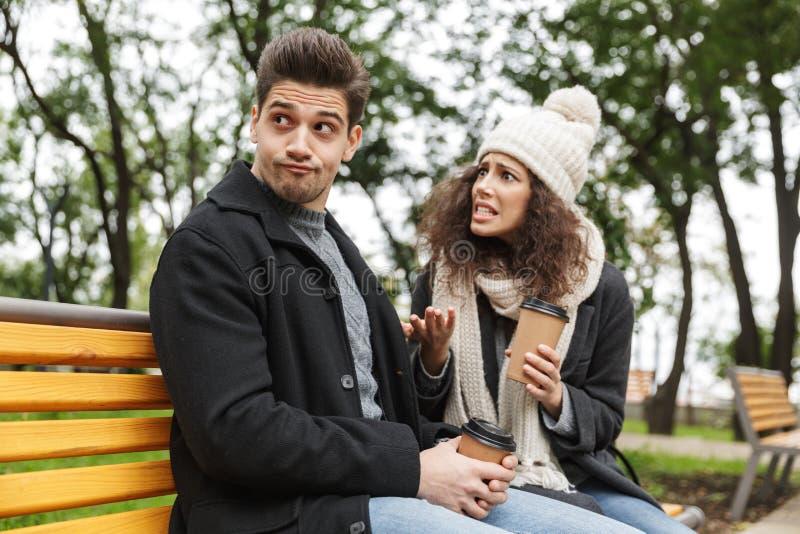 Displeased forçou o ar livre bebendo de amor novo do chá ou do café dos pares no parque que fala um com o otro a discussão fotografia de stock