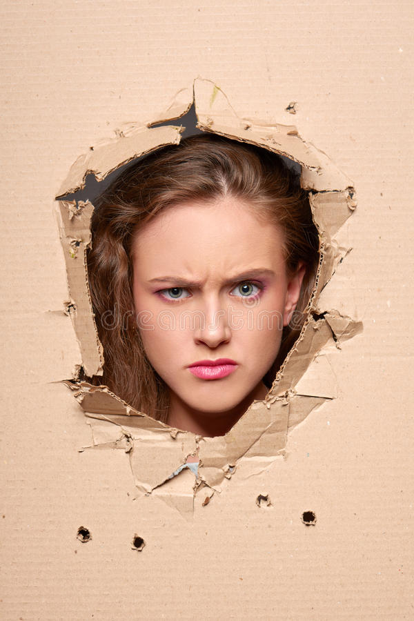 Displeased girl peeping through hole in paper royalty free stock images