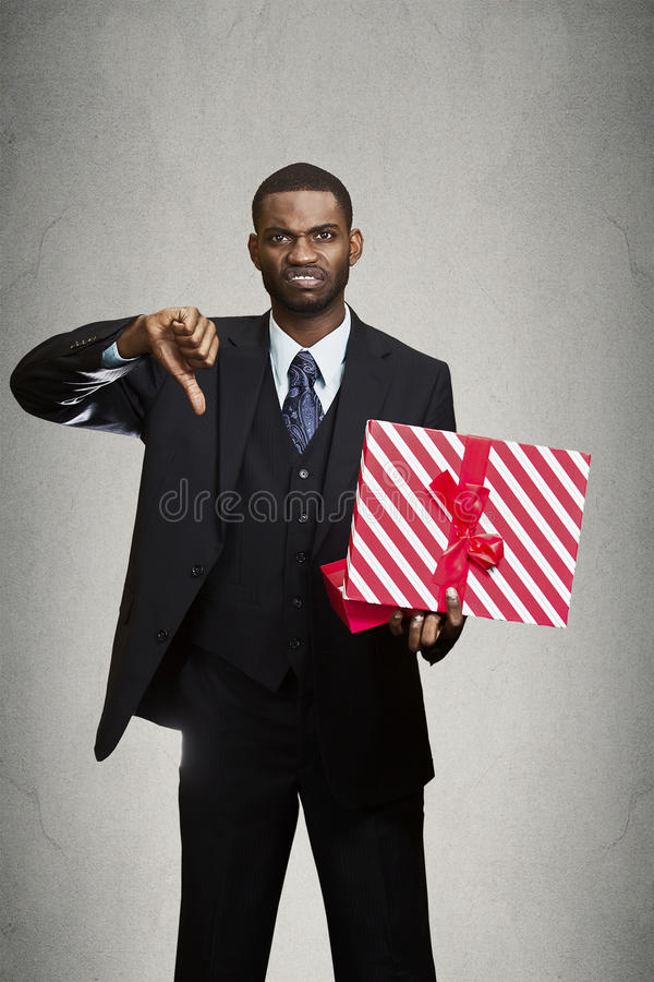 Displeased man giving thumbs down to gift he received. Closeup portrait grumpy unhappy upset man holding gift box displeased with what received disgust on face royalty free stock photos