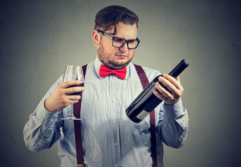 Displeased man looking at a bottle of red wine stock photos