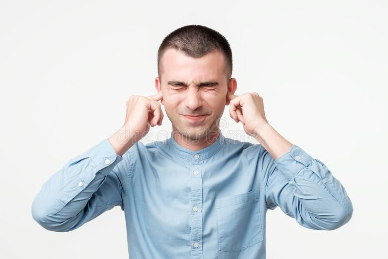 Displeased man plugging ears with fingers. He does not want to listen to arguments. Close up isolated on gray wall background royalty free stock photo