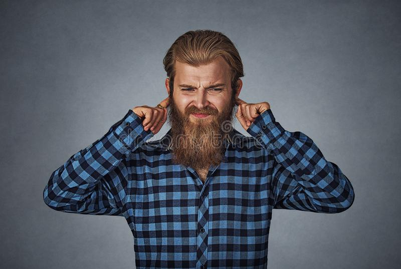 Displeased man plugging ears with fingers don`t want to hear stock photography