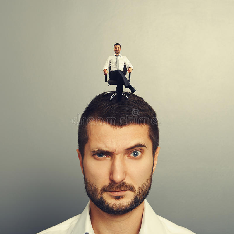 Displeased man with small happy man. Portrait of displeased man with small happy man on the head royalty free stock images