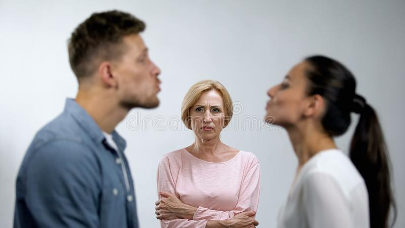 Displeased mother with hands crossed looking at young couple preparing to kiss stock photo