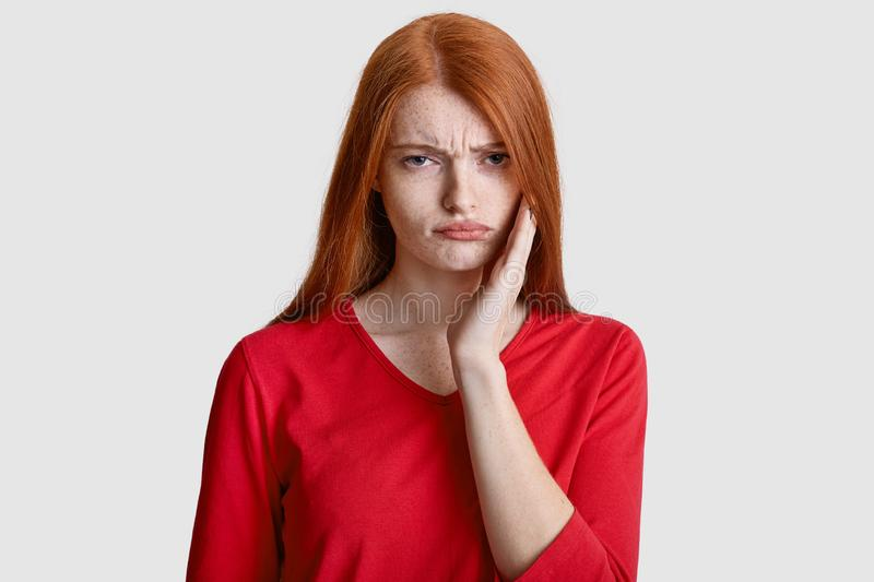 Displeased red haired woman with freckled skin, keeps hand on cheek, suffers from toothache, has sensitivity, wears casual red stock photos
