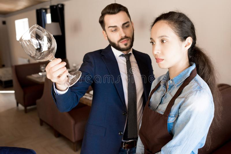 Displeased restaurateur showing dirty wineglass to waitress. Discontent handsome male restaurateur in formal jacket reporting young waitress for dirty wineglass stock image