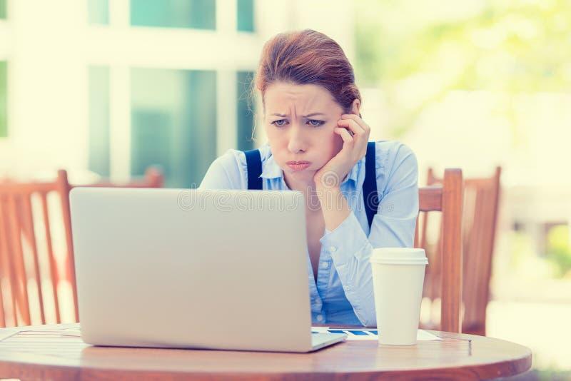 Displeased sorgte sich die Geschäftsfrau, die vor Laptop-Computer sitzt lizenzfreie stockbilder