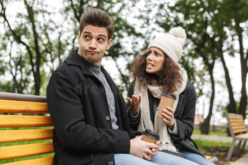 Displeased subrayó aire libre de consumición del té o del café de los pares cariñosos jovenes en el parque que hablaba con uno a  fotografía de archivo