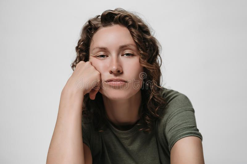 Displeased tired sleepy curly woman, propping his cheek, looking bored royalty free stock photography
