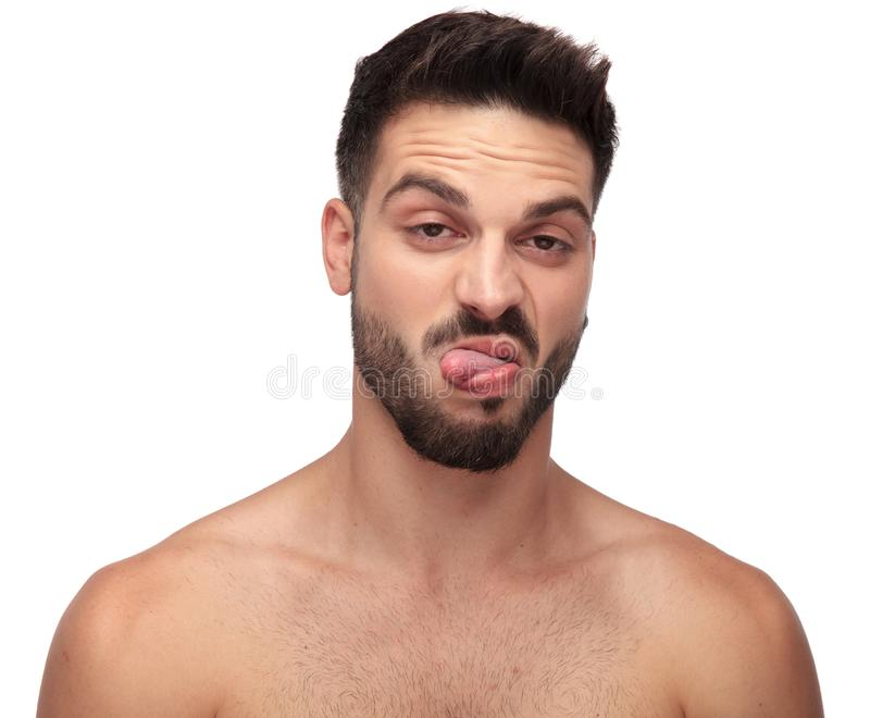 Displeased undressed man being goofy with tongue out. On white background royalty free stock images