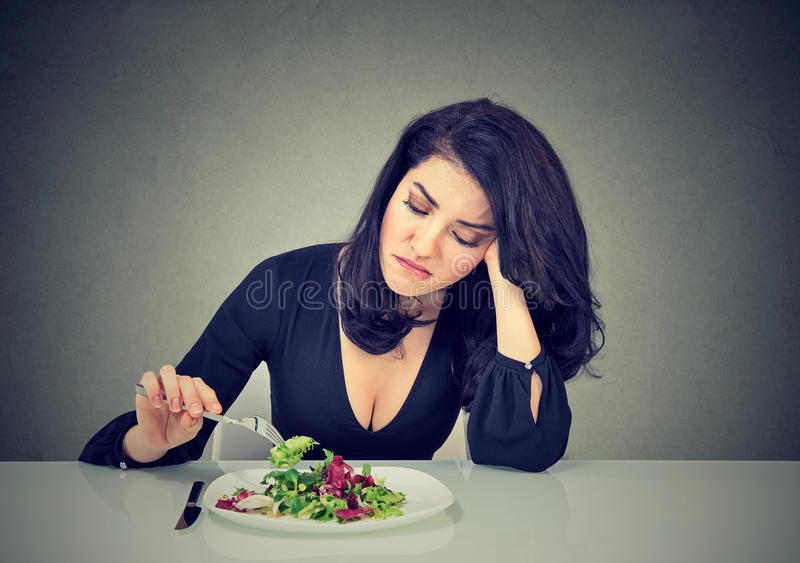 Displeased woman eating green leaf lettuce tired of diet restrictions. Displeased young woman eating green leaf lettuce tired of diet restrictions royalty free stock photography