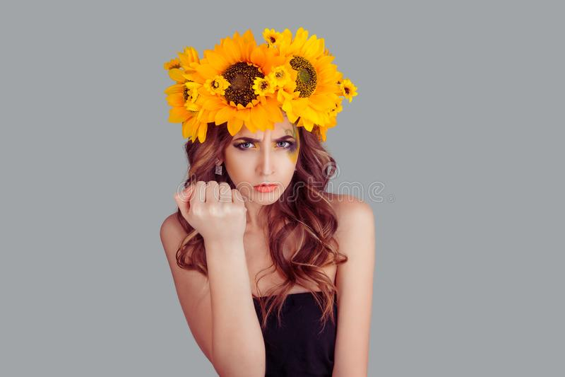 Displeased Woman with floral headband showing fist in anger royalty free stock photography
