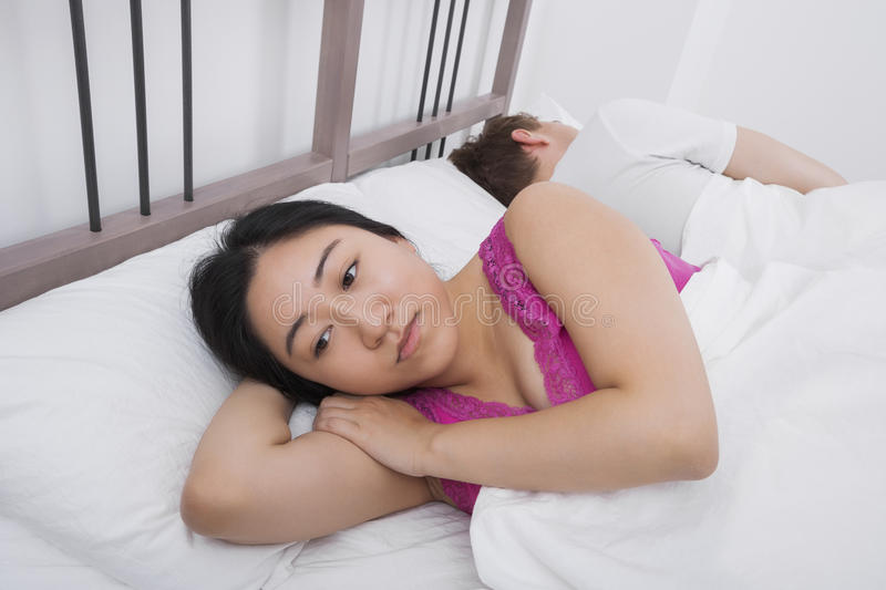 Displeased woman with man sleeping in bed. Displeased women with men sleeping in bed royalty free stock photography