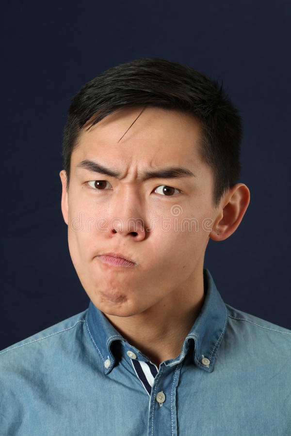 Displeased young Asian man making face stock image