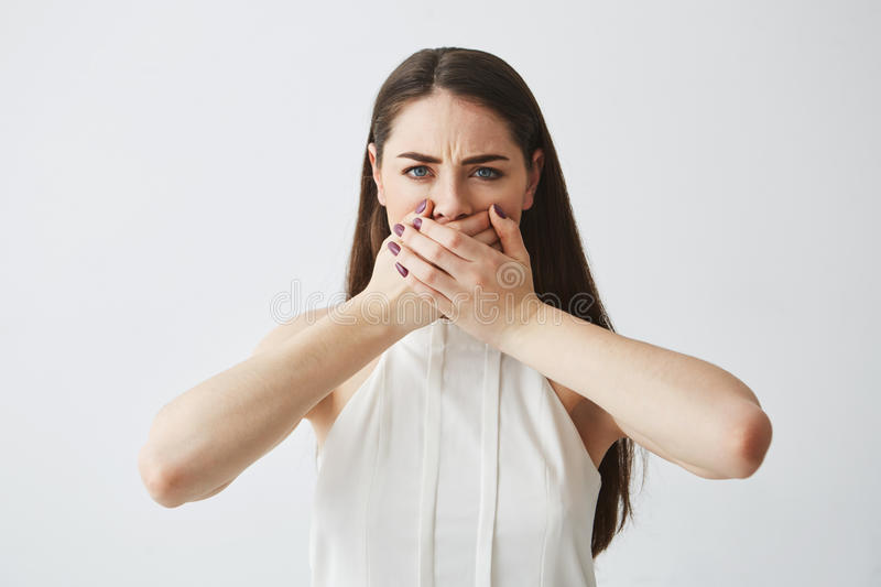 Displeased young brunette girl covering mouth with hand looking at camera over white backround. stock images