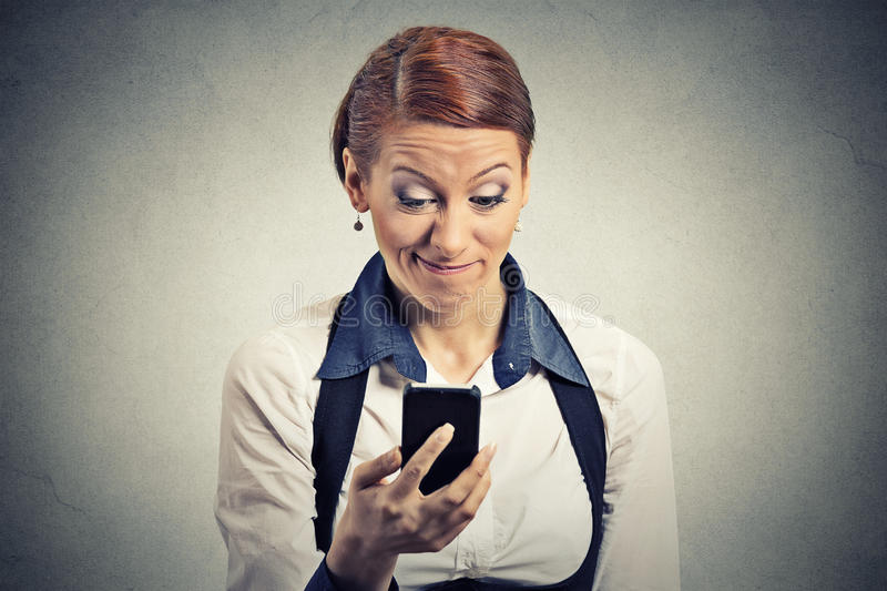 Displeased young businesswoman reading bad news on smart phone stock photography