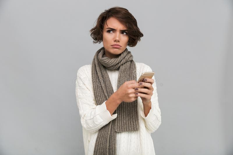 Displeased young lady wearing scarf chatting by mobile phone. Image of displeased young lady wearing scarf standing isolated over grey background. Looking aside stock images