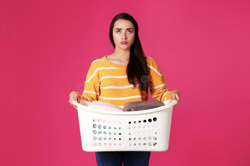 Displeased young woman holding basket with laundry stock photo