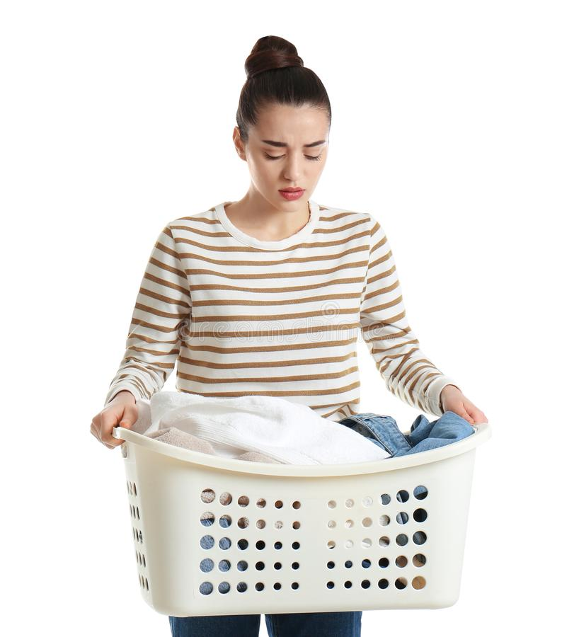 Displeased young woman holding basket with laundry royalty free stock photo