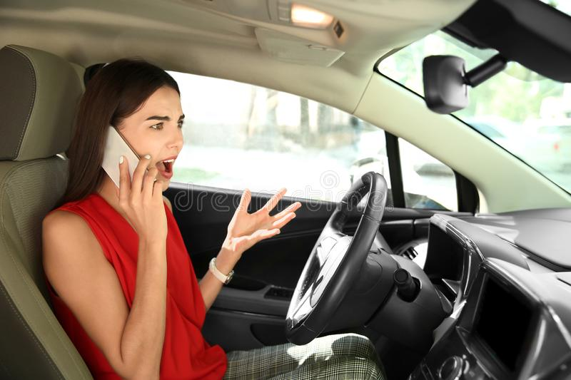 Displeased young woman talking by mobile phone on driver's seat of car royalty free stock images