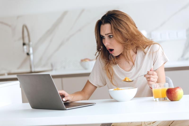 Displeased young woman using laptop in kitchen royalty free stock photos