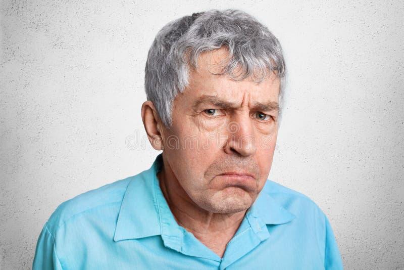 Displesed不快乐的起皱纹的成熟男性皱眉面孔并且弯曲嘴唇,穿正式衬衣,摆在反对白色具体背景 C 免版税图库摄影