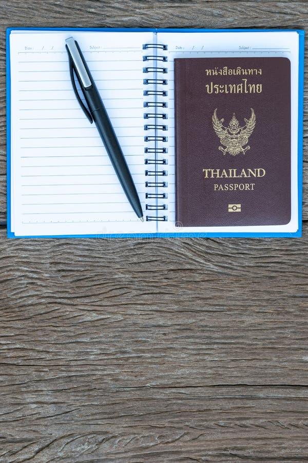 Disponga la penna ed il passaporto della Tailandia ad una pagina in bianco di un noteboo fotografia stock libera da diritti