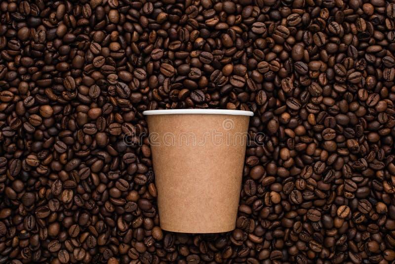 Disponibel kopp kaffe för hantverk som går på bakgrunden av grillade bönor fotografering för bildbyråer