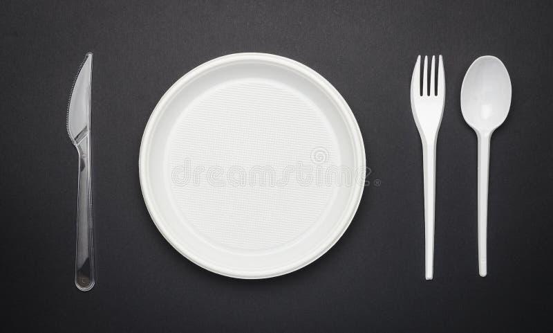 Disponibel plast- bordsservis, gaffel, kniv, sked och platta på svart bakgrund fotografering för bildbyråer