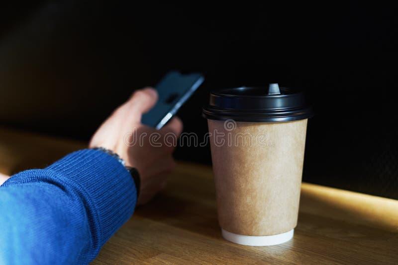Disponibelt pappers- exponeringsglas med kaffe, affärsmannen som använder smartphonen, medan ha vila, bryter eller äter lunch arkivbilder