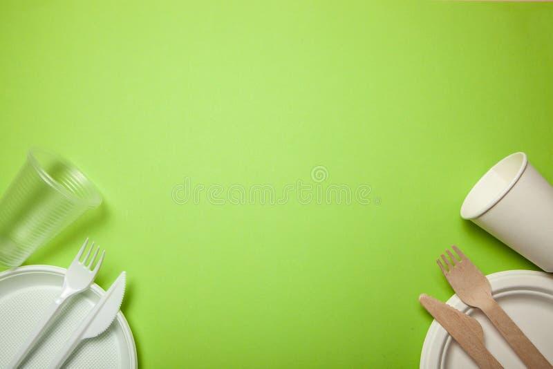 Disponibla redskap för plast- som och Eco-vänskapsmatch göras av bambuträ och papper på en gräsplan gaffel knivar, plattor, koppa royaltyfria foton