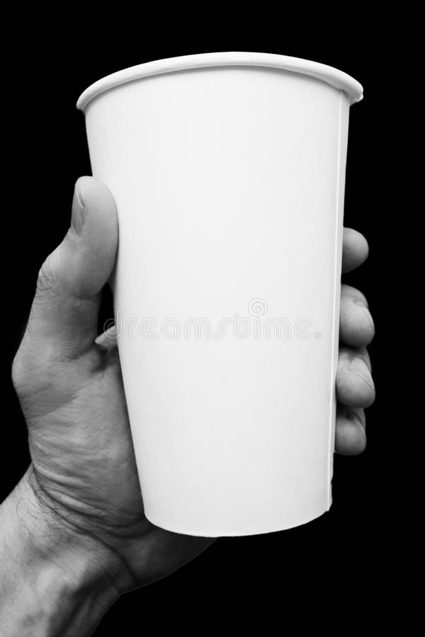 The disposable cardboard cup in hand. On black background stock photo