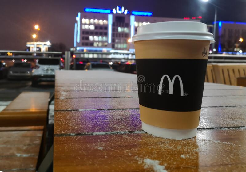 Disposable coffee glass with logo McDonald`s in winter in fast food restaurant McDonald`s on the background of night city stock images