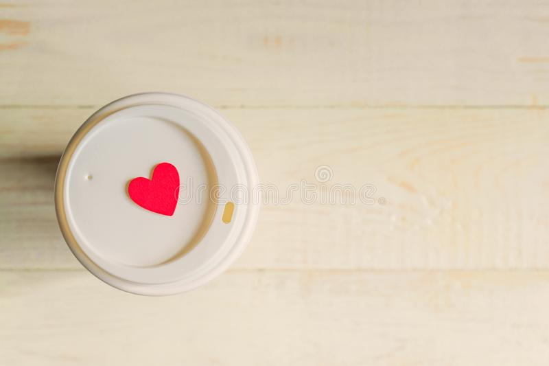 Disposable craft paper coffee cup and red wooden heart on a cap. Coff to go on wooden table royalty free stock photo