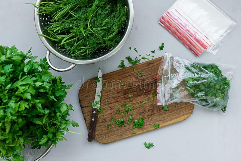 Disposable package with chopped fresh green parsley and dill or fennel on gray wooden table. Top view. Copy space. Harvesting. Concept stock photography