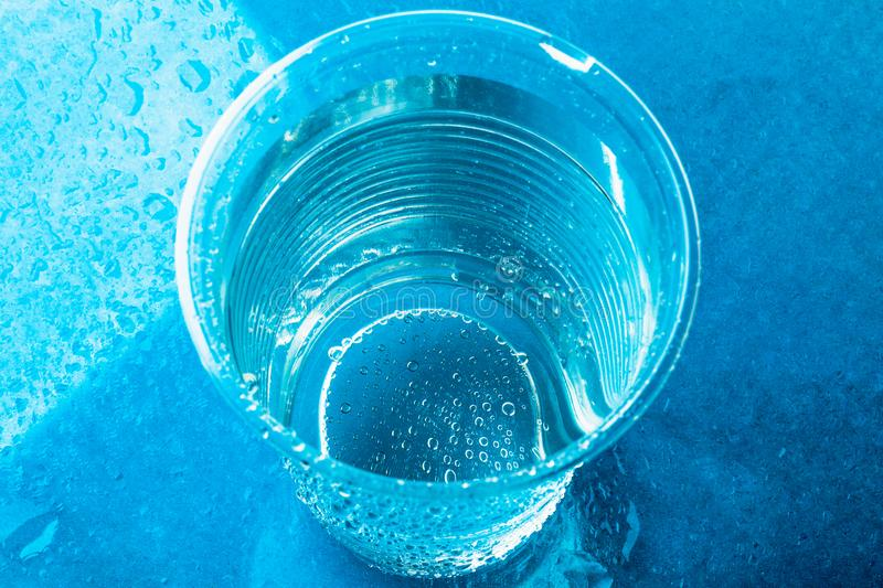 Disposable plastic glass or cup with fresh clear water on bright blue background, top view royalty free stock image