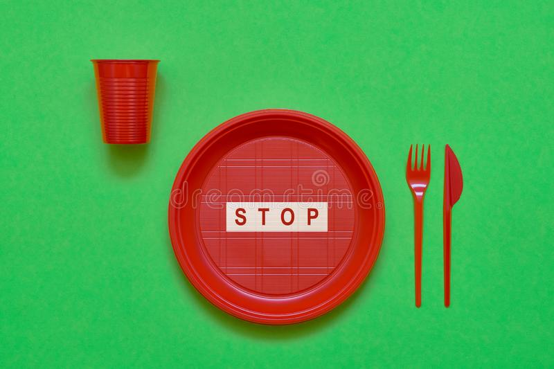 Disposable red plastic plate with word STOP inside, red knife and fork on green background. Top view, copy space. Plastic free royalty free stock images