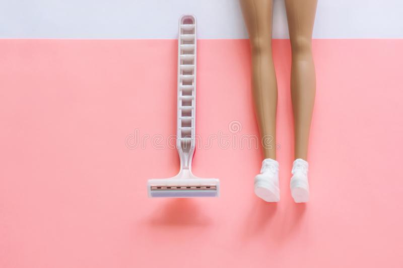 Disposable shaving machine for women on a pink pastel background, flatley, copy space. Disposable shaving machine for women and dolls legs on a pink and white stock images